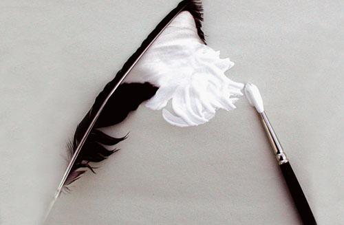 pincel pintando de blanco una pluma de pájaro