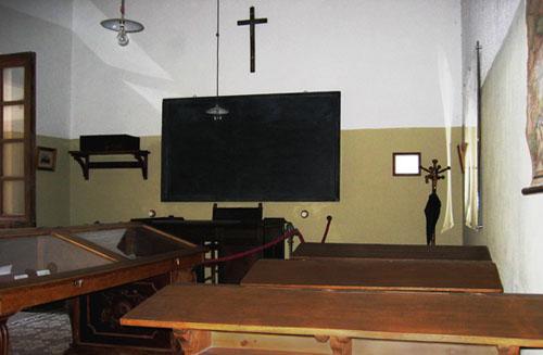 Aula antigua con pupitres, pizarra y crucifijo
