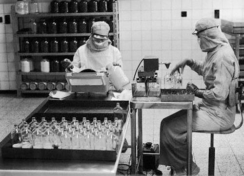 Imagen en blanco y negro de dos personas trabajando en un laboratorio farmaceutico