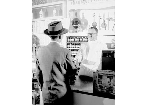Imagen en blanco y negro de un hombre comprando medicamentos en una farmacia