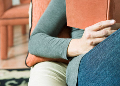 Imagen de un torso de una mujer sentada en un sofá mientras lee. Corbis