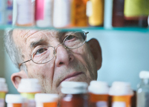 Imagen de un hombre de unos setenta años de edad trás unos botes de medicamentos
