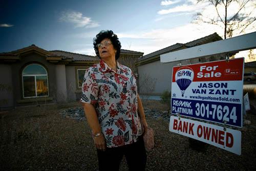 Imagen de una mujer deshauciada junto al cartel de 'se vende, propiedad del banco' en EEUU