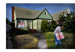 Imagen de un señor colocando un cartel de 'se vende' frente a una casa