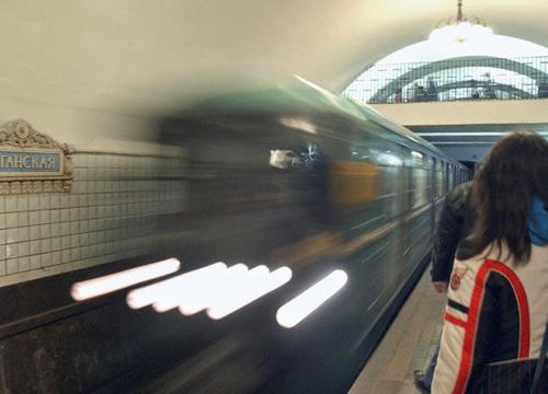 Imagen del metro de Moscú. En el andén, una mujer de espaldas esperando mientras pasa un tren