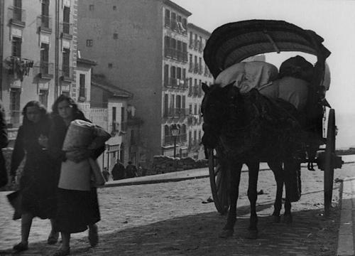 Dos mujeres andando junto a un carro de caballos en Madrid durante la Guerra Civil española