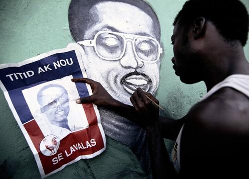 Haitiano copiando el retrato de Aristide en una fachada de Puerto Príncipe