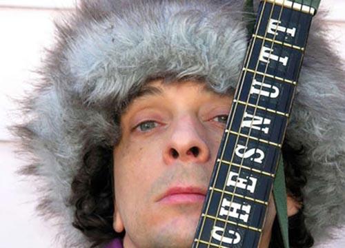 Vic Chesnutt con el mástil de su guitarra apoyado en la cara