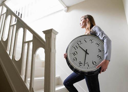 Mujer subiendo por las escaleras con un gran reloj entre las manos
