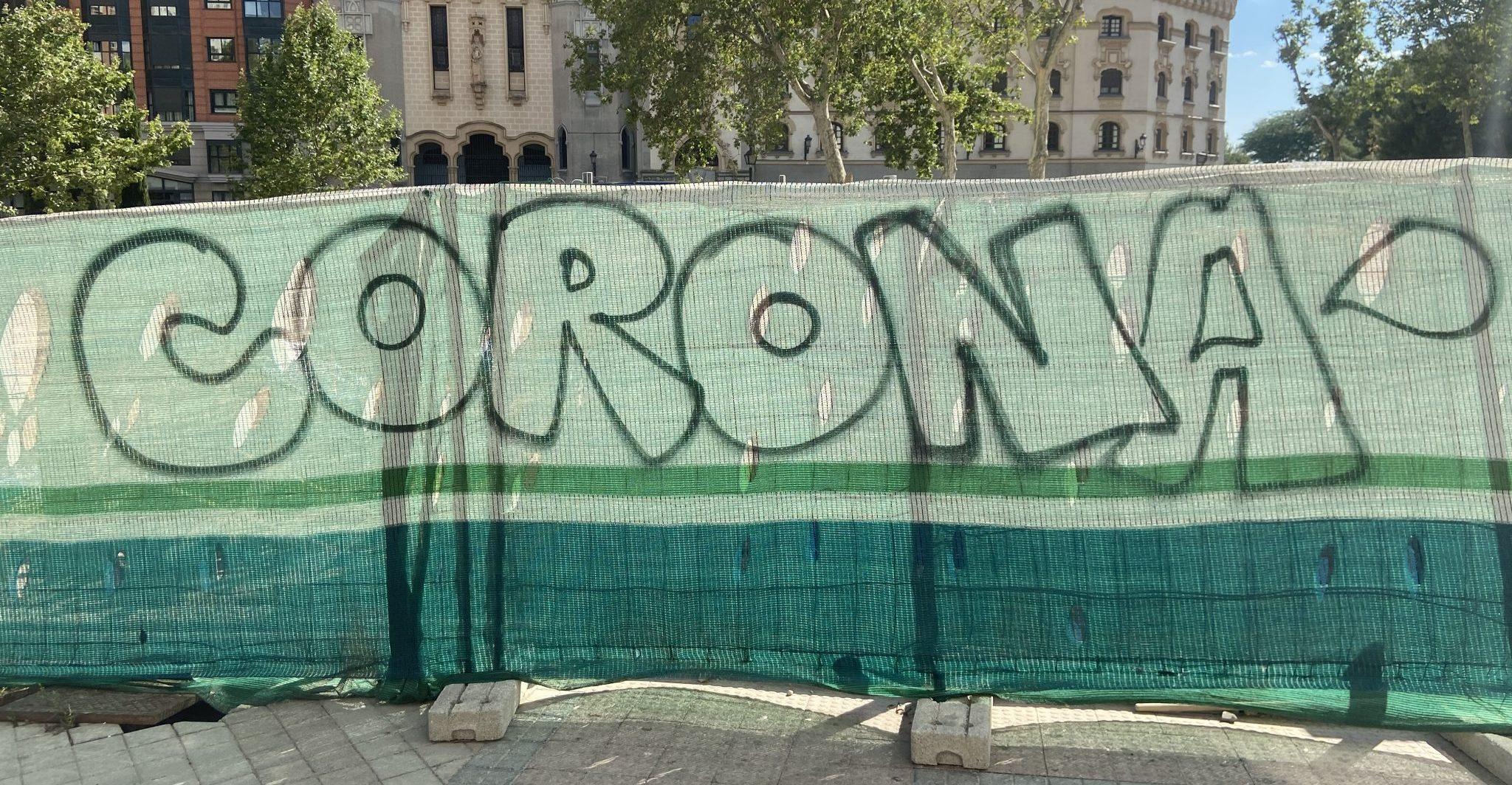 «CORONA», escrito así, en mayúsculas, en una lona de obra de Madrid.