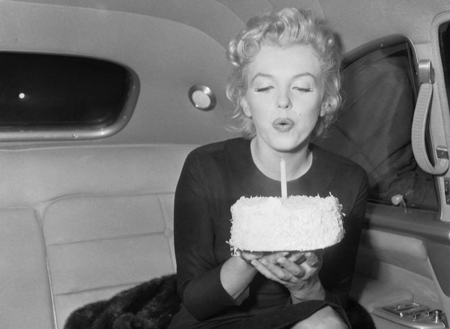 Marilyn Monroe soplando soñando: soplando una vela del pastel de cumpleaños.